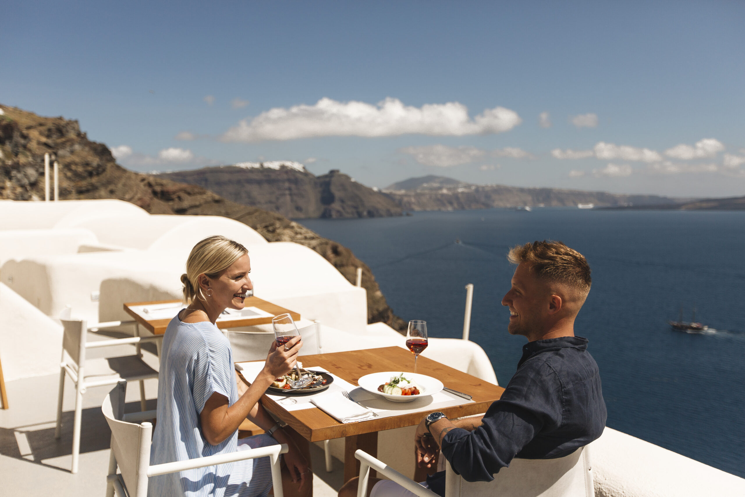 Couple enjoying delicious breakfast at Charisma restaurant of Mystique Hotel in Santorini