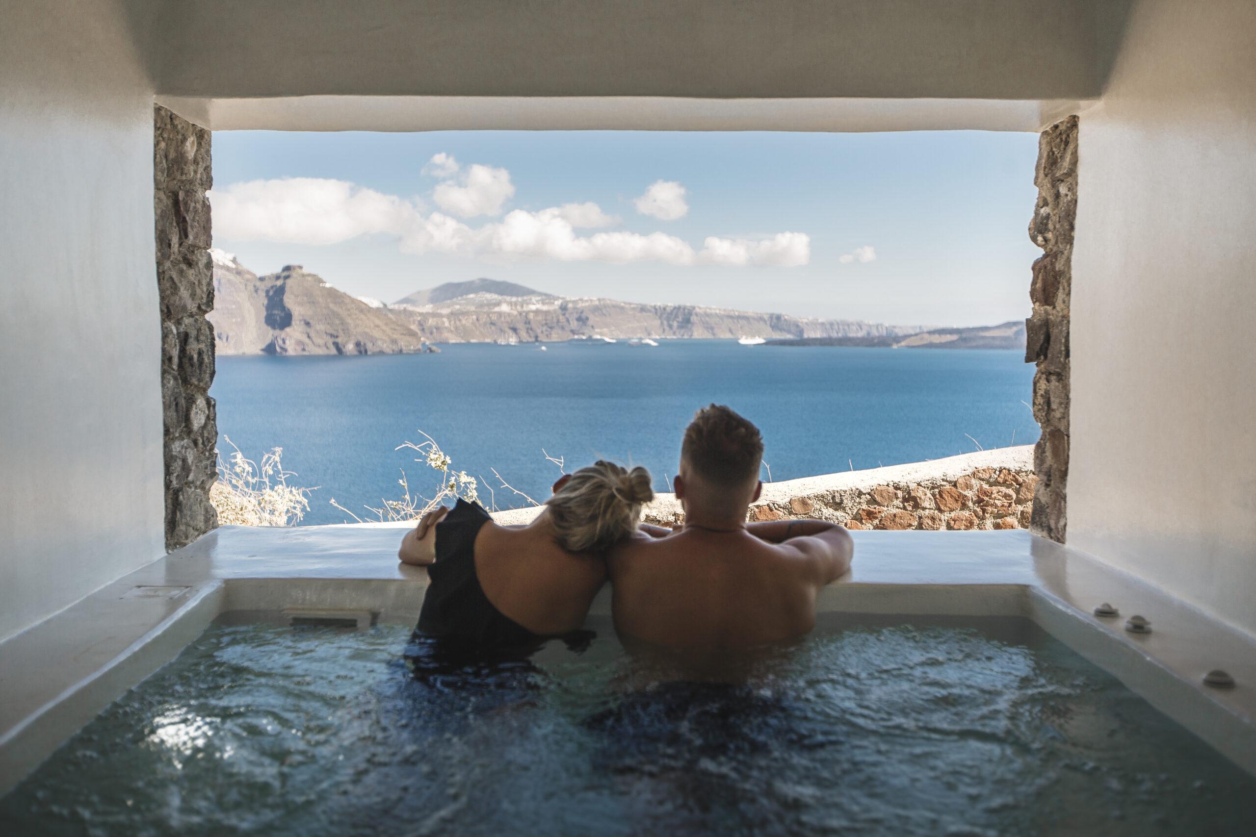 Couple in private jacuzzi enjoy sea view in Santorini