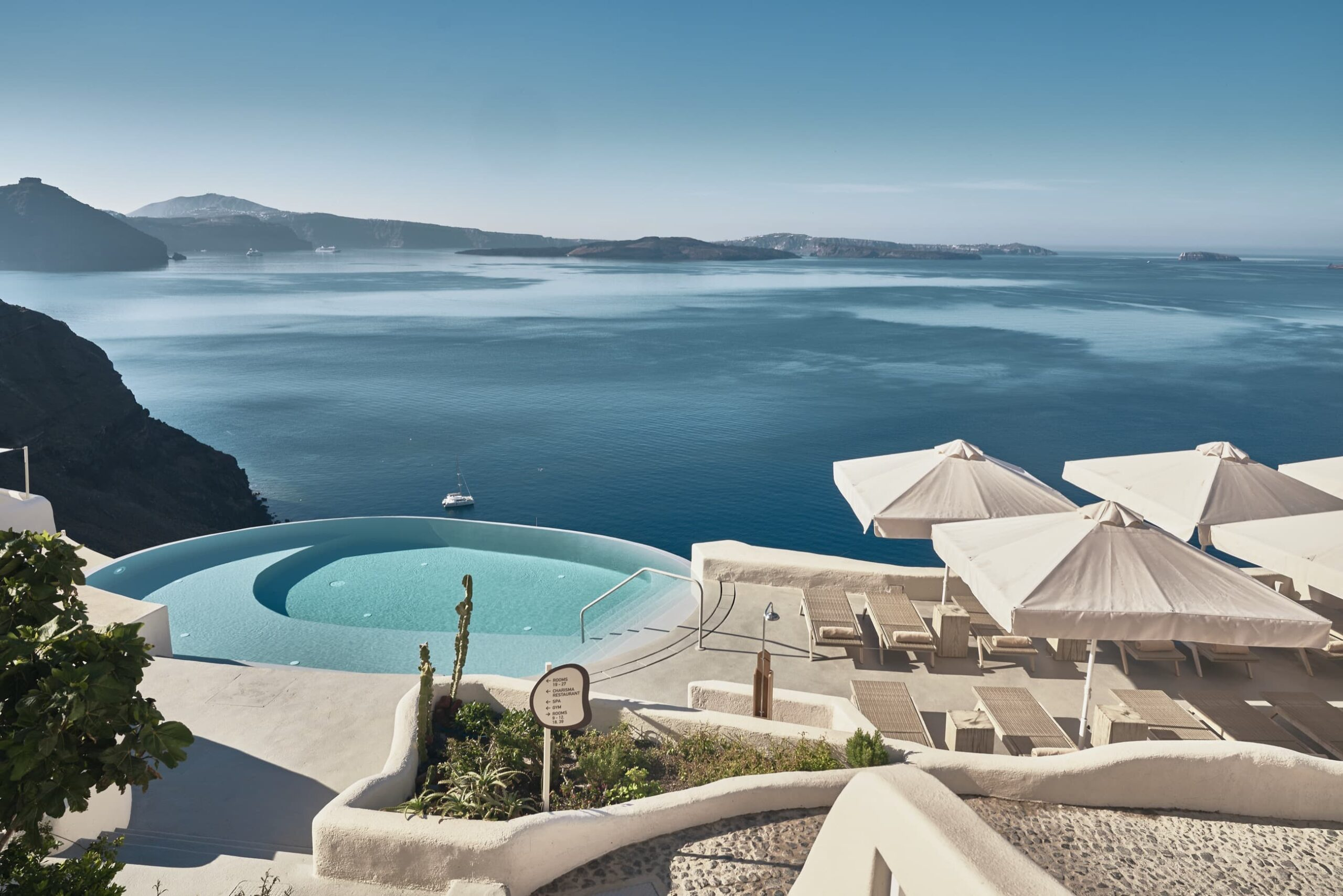 Infinity pool of Mystique Hotel with view over the volcano of Santorini